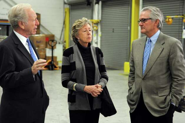 Senator Joseph Lieberman, left, and his wife, Hadassah, get a tour of AmeriCares from President and CEO Curt Welling in Stamford on Wednesday, October 10, 2012. Photo: Lindsay Niegelberg / Stamford Advocate