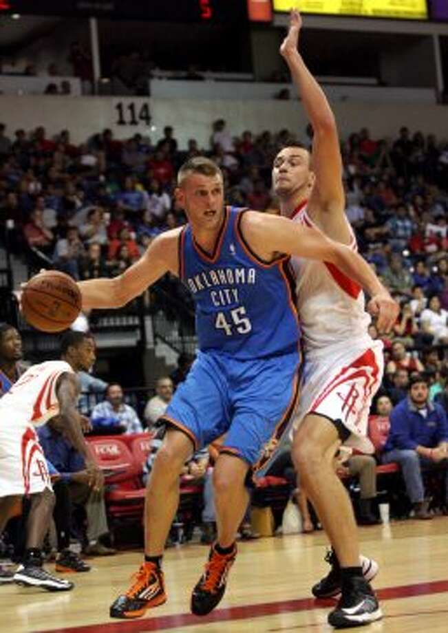 Oklahoma City Thunder's Cole Aldrich (45) drives on Houston Rockets' Donatas Motiejunas during the second quarter of an NBA preseason basketball game in Hidalgo, Texas, Wednesday, Oct. 10, 2012. The Thunder won 107-103. (AP Photo/Delcia Lopez) (Associated Press)