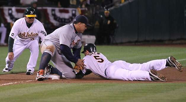 Trying to stretch his double, A's shortstop Stephen Drew made the first out of the sixth inning when he was tagged at third base by the Tigers' Miguel Cabrera. Photo: Lance Iversen, The Chronicle