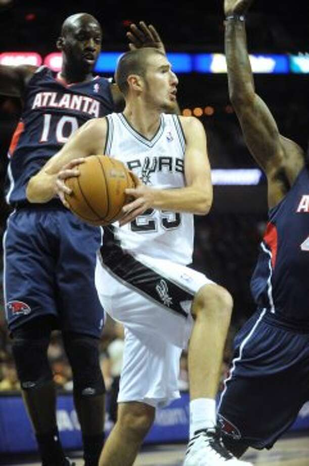 Nando de Colo of the Spurs passes off against Atlanta during preseason NBA action at the AT&T Center on Wednesday, Oct. 10, 2012. (Billy Calzada / San Antonio Express-News)