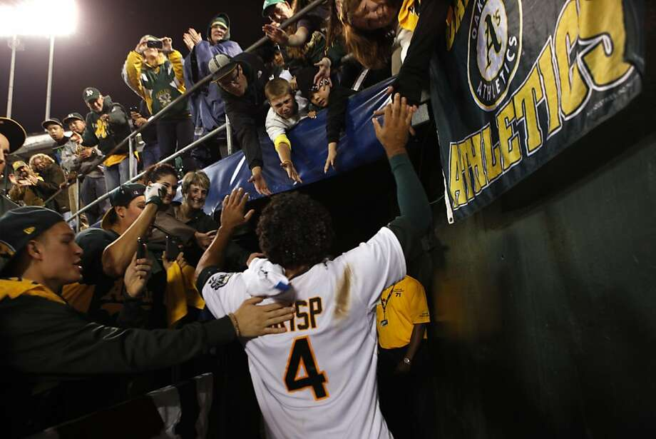 A's center fielder Coco Crisp celebrates with fans after his single scored the winning run to beat the Detroit Tigers 4-3 in Game 4 of their playoff series. Photo: Beck Diefenbach, Special To The Chronicle
