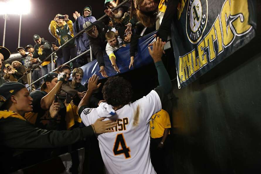A's center fielder Coco Crisp celebrates with fans after his single scored the winning run to beat t