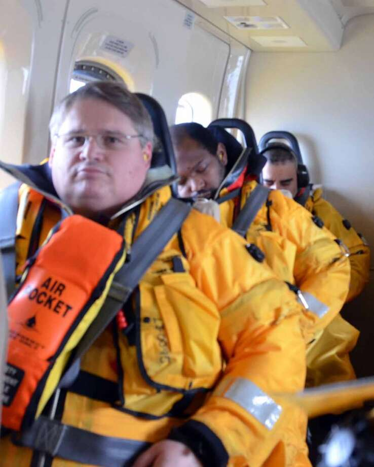 Donald LeCourt, Shell Alaska's wells HSE team leader, and other workers take a helicopter ride to the Noble Discoverer during a crew change on Oct. 9, 2012. In preparation for the hour-long flights over frigid Arctic waters, crew members must complete helicopter underwater escape training and don one-piece Mustang Survival immersion suits filled with foam for insulation and buoyancy.  (Photo: Jennifer A. Dlouhy / The Houston Chronicle) (Jennifer A. Dlouhy)