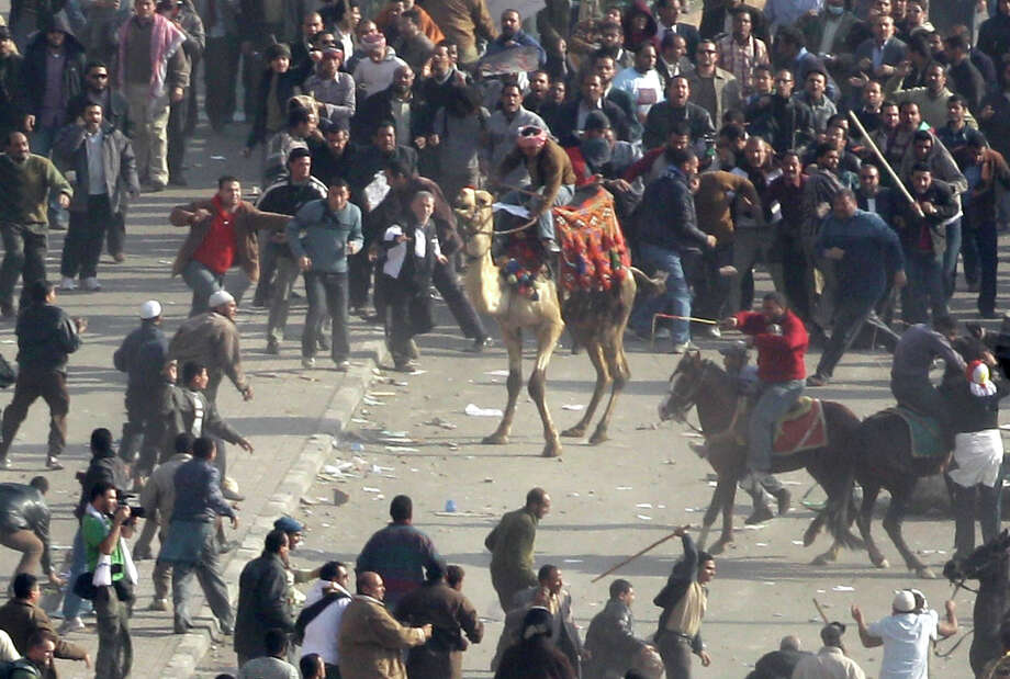 FILE - In this Wednesday, Feb. 2, 2011 file photo, pro-government demonstrators, some riding camels and horses and armed with sticks, clash with anti-government demonstrators in Tahrir square, the center of anti-government demonstrations, in Cairo, Egypt. Egypt's state news agency said Wednesday, Oct. 10, 2012 that a Cairo court has acquitted 25 loyalists of ousted President Hosni Mubarak loyalists who had been accused of organizing an attack in which assailants on horses and camels charged into crowds of anti-regime protesters last year. (AP Photo/Ben Curtis, File) Photo: Ben Curtis