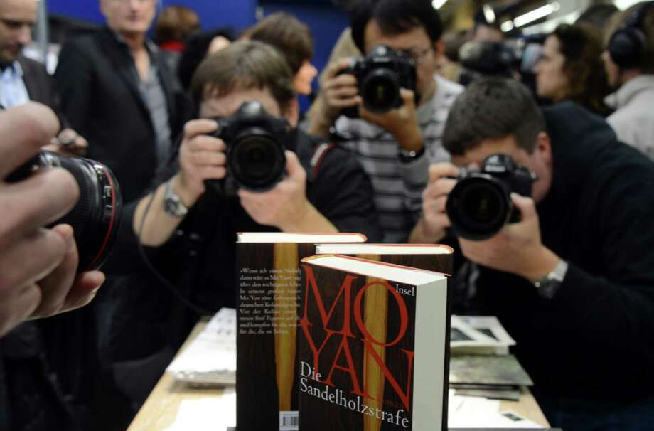 Photographers take pictures of books of Chinese author Mo Yan's, the 2012 Nobel Literature Prize winner, at the Unionsverlag booth at the 64th Frankfurt Book Fair on Thursday, Oct. 11, 2012. Photo: JOHANNES EISELE, AFP/Getty Images / AFP