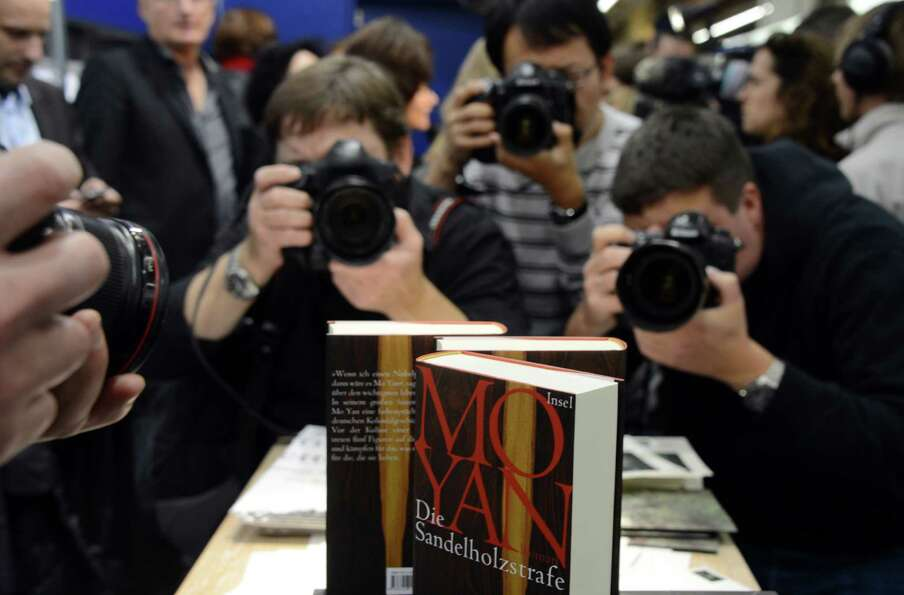Photographers take pictures of books of Chinese author Mo Yan's, the 2012 Nobel Literature Prize win