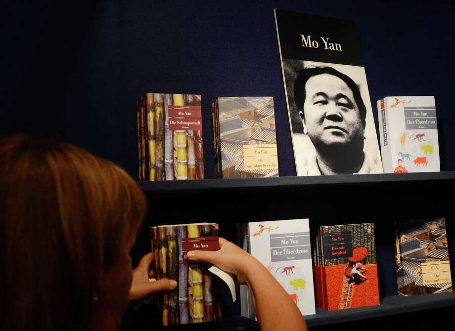 A woman places a poster of Chinese author Mo Yan, the 2012 Nobel Literature Prize winner, at the Unionsverlag booth at the 64th Frankfurt Book Fair on October 11, 2012. Mo Yan won the Nobel Literature Prize for writing that mixes folk tales, history and the contemporary, the Swedish Academy announced Thursday. Photo: JOHANNES EISELE, AFP/Getty Images / AFP