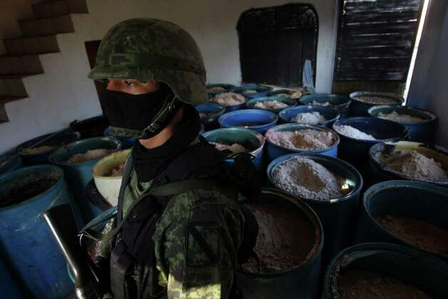 "FILE - In this Feb. 9, 2012, file photo a soldier stands in a room full of barrels containing white and yellow powder after a seizure of 15 tons of pure methamphetamine at a small ranch in Tlajomulco de Zuniga, on the outskirts of Guadalajara, Mexico. Mexican drug cartels are flooding U.S. cities with cheap, extraordinarily pure methamphetamine made in factory-like ""super labs"" _ a surge in production that has all but negated the nation's long effort to curb meth production at home with tighter controls on key ingredients.  (AP Photo/Bruno Gonzalez, File) Photo: Bruno Gonzalez, STR / ap"