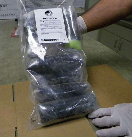 In this Sept. 7, 2012, photo a U.S. Drug Enforcement Administration technician holds several pounds of Mexican meth confiscated in the St. Louis area. Methamphetamine has long been a significant problem in the United States, but the DEA says the influx of meth from south of the border is offsetting any gains made against clandestine meth labs in the U.S. DEA statistics show that the Mexican cartels are making the meth more pure, creating a faster and easier high for users, and they?re selling it more cheaply in hopes of creating a new market. Seizures at the border and in several U.S. cities are up sharply. (AP Photo/Jim Salter) Photo: Jim Salter, STF / AP