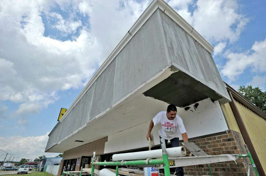 Joe Esqueda, who works for Sam's Build Out Solutions, adds more new stucco to a building being remodeled at 3404 Washington Blvd. Washington Boulevard may be seeing a reconstruction from MLK Blvd. to IH-10 in the future paid for by the natural gas royalties that Beaumont has.  Dave Ryan/The Enterprise