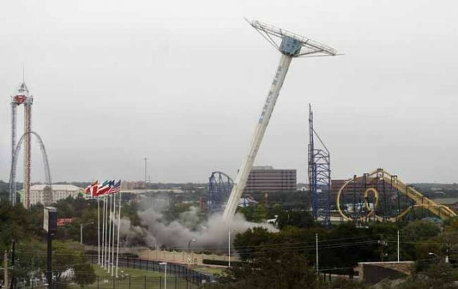 The Texas Chute Out ride falls over as planned during an implosion by the Dallas Demolition Company at Six Flags Over Texas amusement park Wednesday, Oct. 10, 2012, in Arlington, Texas. The 200-foot-tall ride opened at the amusement park in 1976 and was modeled after the old parachute drop at Coney Island. The ride was demolished in preparation for the park's newest attraction, the Texas SkyScreamer which is scheduled to be completed in 2013. (AP Photo/Tony Gutierrez) (Tony Gutierrez / Associated Press)