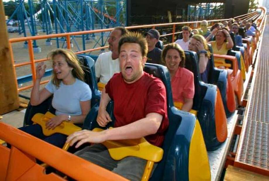 As the coaster car pulls in the station, actor Matthew Perry shows his reaction after riding the new Titan roller coaster at Six Flags over Texas, Thursday, May 10, 2001 in Arlington, Texas.. Perry is in Dallas this week filming his upcoming movie, Servicing Sarah. With Perry is his publicist Christina Papadopoulos. (AP Photo/Six Flags Over Texas/Tom Fox) (TOM FOX / AP)
