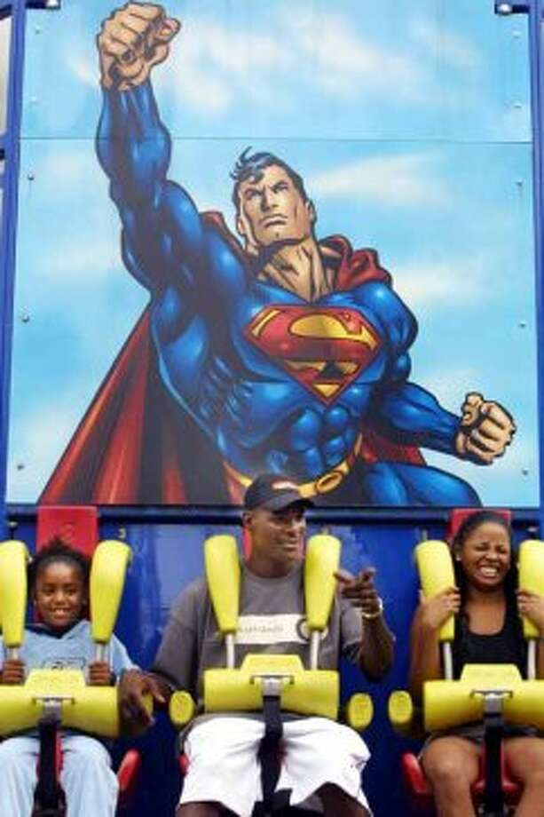 Dallas Cowboys wide receiver Keyshawn Johnson, left, sits with his daughter, Maia, left, and wife, Shikiri, after they enjoyed the Superman Tower of Power ride at Six Flags Over Texas in Arlington, Texas, Monday, Sept. 6, 2004. (AP Photo/Six Flags Over Texas, Jerry W. Hoefer) (JERRY W. HOEFER / AP)