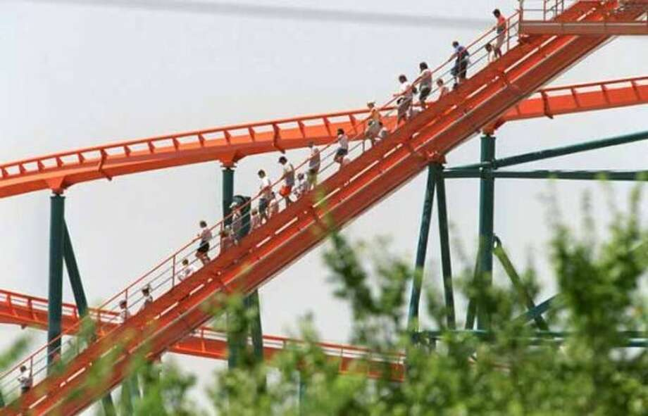 Riders are evacuated from the Titan rollercoaster at Six Flags Over Texas in Arlington, Texas, Wednesday, July 18, 2001. At least 28 thrillseekers riding the rollercoaster at the theme park were stranded at the ride's 225-foot summit for about an hour Wednesday. There were no injuries reported among the passengers in the car that became stuck about 11 a.m. The passengers were stranded as the temperatures soared into the 90s. (LAWRENCE JENKINS / AP)