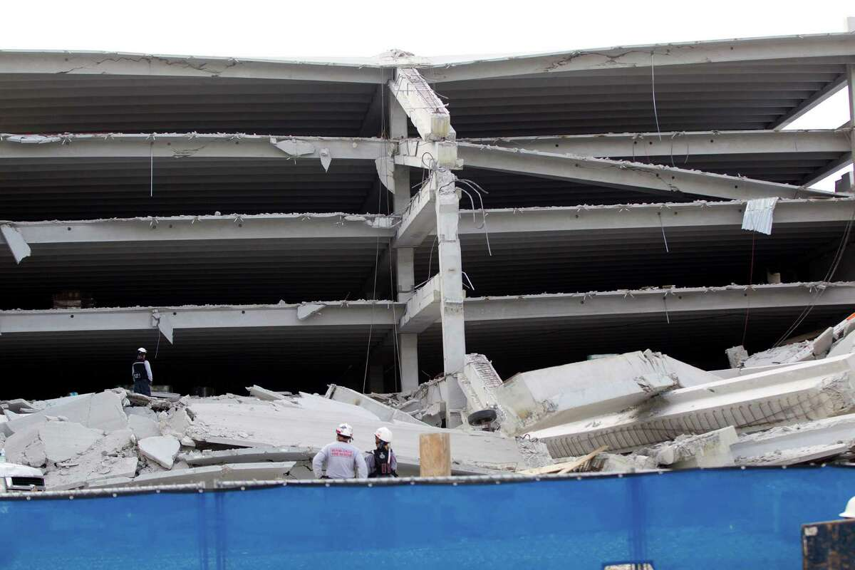 Fire Rescue officials search for victims trapped in the collapsed parking garage at the Miami Dade College West campus in Doral, Fla. Tuesday, Oct. 10, 2012 (AP Photo/J Pat Carter)