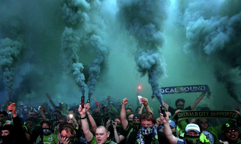 Members of the Emerald City Supporters march to the match between the Seattle Sounders and Portland