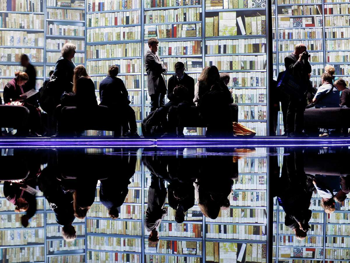 Visitors watch video screens in the New Zealand pavilion on the second day of the Book Fair in Frankfurt, Germany, Thursday, Oct. 11, 2012. New Zealand is this year's guest of honor.