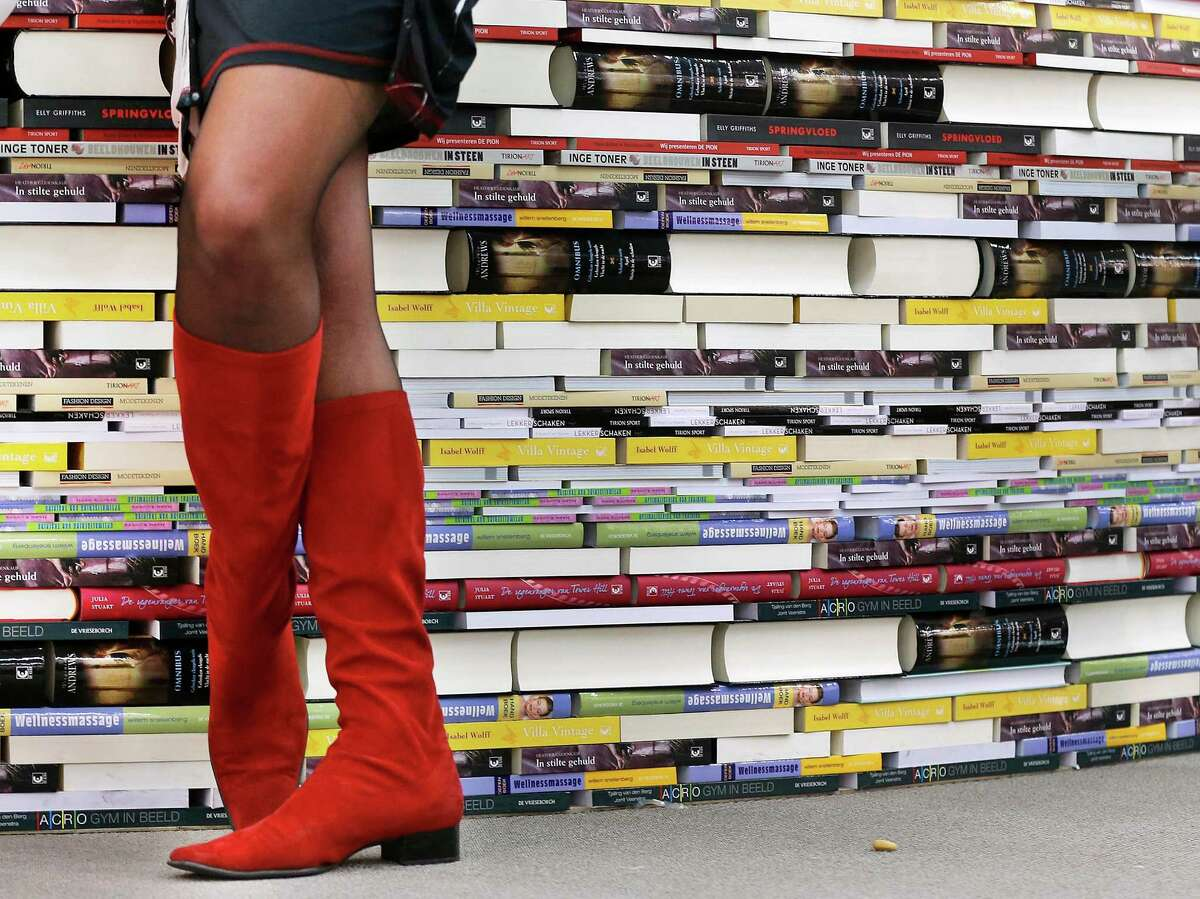 A woman wearing red boots stands next to books on the second day of the Book Fair in Frankfurt, Germany, Thursday, Oct. 11, 2012. New Zealand is this year's guest of honor.