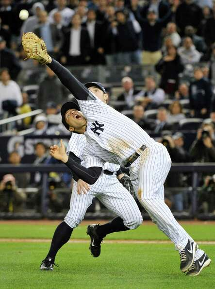 New York Yankees' Mark Teixeira, front, and David Robertson are unable to catch a pop fly hit by Bal