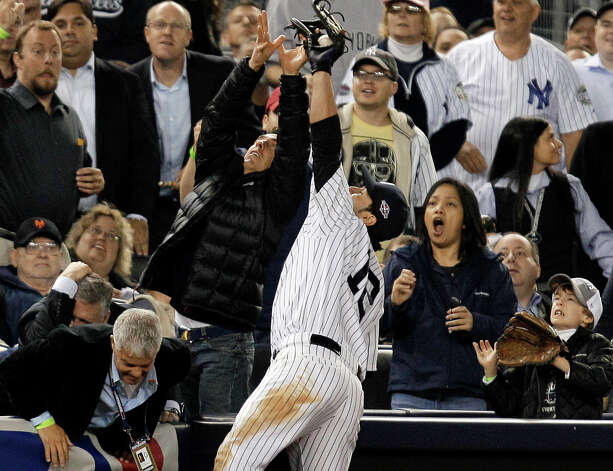 New York Yankees third baseman Eric Chavez competes with fans as he catches a ball hit into foul territory by Baltimore Orioles' Manny Machado for an out during the seventh inning of Game 3 of the American League division baseball series Wednesday, Oct. 10, 2012, in New York. Photo: Kathy Willens, AP / AP
