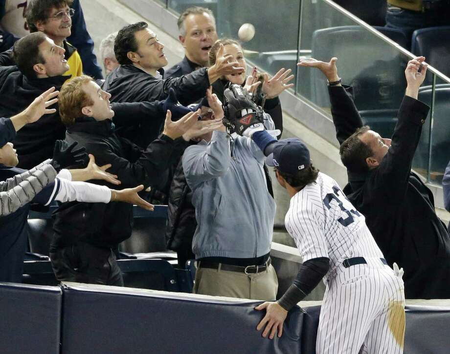 New York Yankees' Nick Swisher reaches into the stands for a foul ball hit by Baltimore Orioles' J.J. Hardy in the 11th inning of Game 3 of the American League division baseball series on Wednesday, Oct. 10, 2012, in New York. Swisher was unable to make the catch. Photo: Peter Morgan, AP / AP