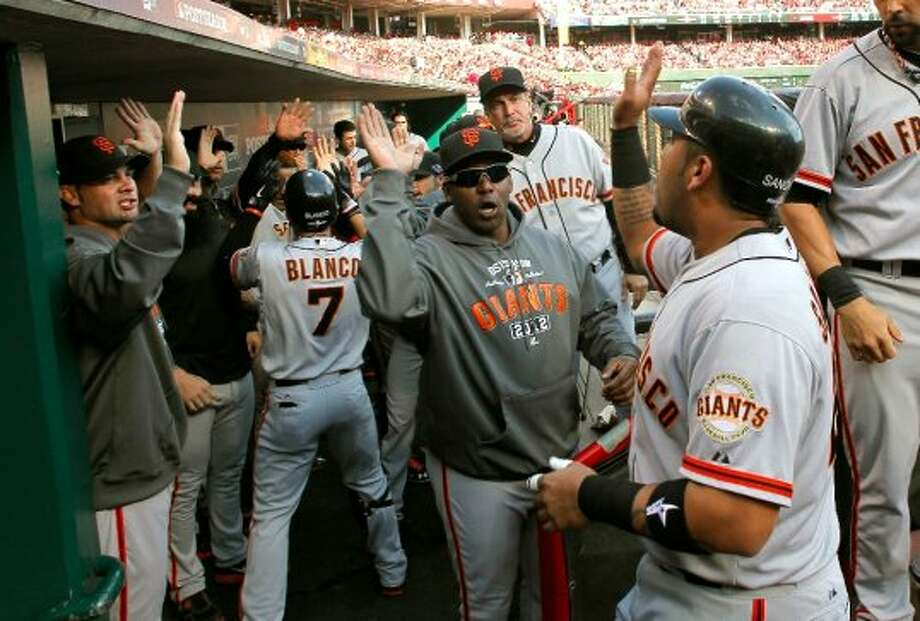 The Giants bench celebrates two run home run by Gregor Blanco, (left)  in the second inning that scored teammate Hector Sanchez, as the San Francisco Giants take a 2-1 lead on the Cincinnati Reds in game four of the National League Division Series in Cincinnati, Ohio on Wednesday Oct. 10, 2012. (Michael Macor / The Chronicle)