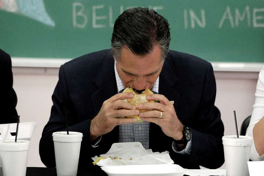 But eating a hamburger in front of a sign that reads Believe in America brings you back on message. (AP) Photo: Jae C. Hong, ASSOCIATED PRESS / AP2012