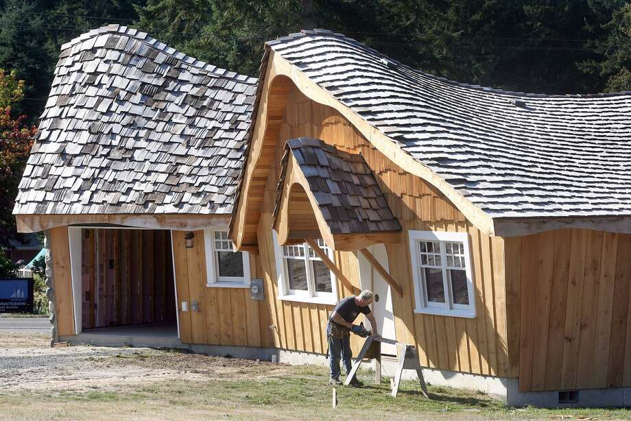 "Chris Whited of Bainbridge Island, Wash. works on his cottage on Bainbridge Island Thursday, Oct. 4, 2012.  The new 1,200-square-foot house already dwarfs two cottages the 59-year-old contractor has built on his property. A few years ago, Whited took a trip to Cannon Beach, Ore., and spotted a garden shed with an oddly sloped roof. When he got home, he decided to use the shed as a model for a very fancy chicken coop. The result was a quaint henhouse with a curved roofline and neatly trimmed windows. ""The neighbors call it a hobbit house, among other things,"" Whited said. Photo: AP"