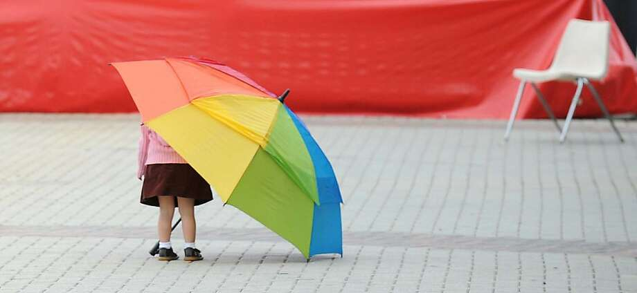 Louisiana light rain: One-year-old June Furlong takes cover under an umbrella on the Red River Revel festival in Shreveport. Photo: Jim Hudelson/The Times, Associated Press