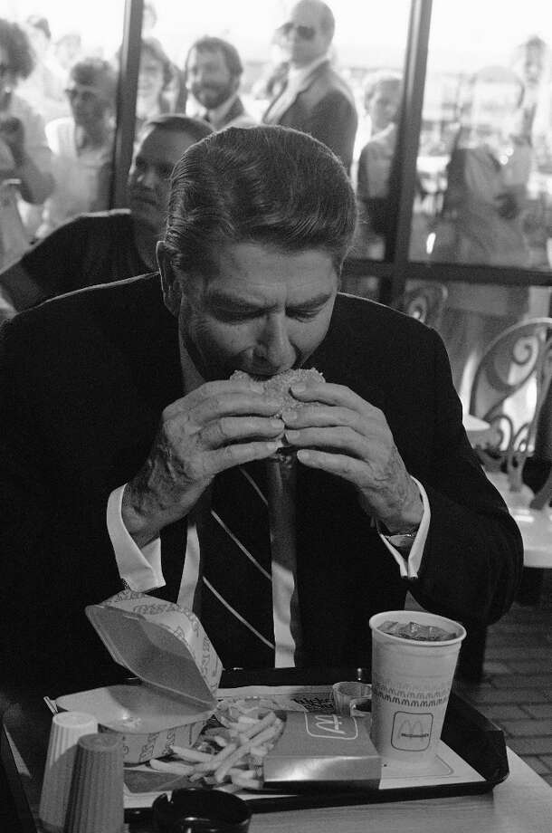"Ronald Reagan – The president who said, ""All great change begins at the dinner table"" had a sweet tooth and loved jelly beans so much he had a portrait of himself made out of his favorite brand, Jelly Belly. He's seen here eating a Big Mac in Alabama. Photo: Lana Harris, ASSOCIATED PRESS / AP1984"