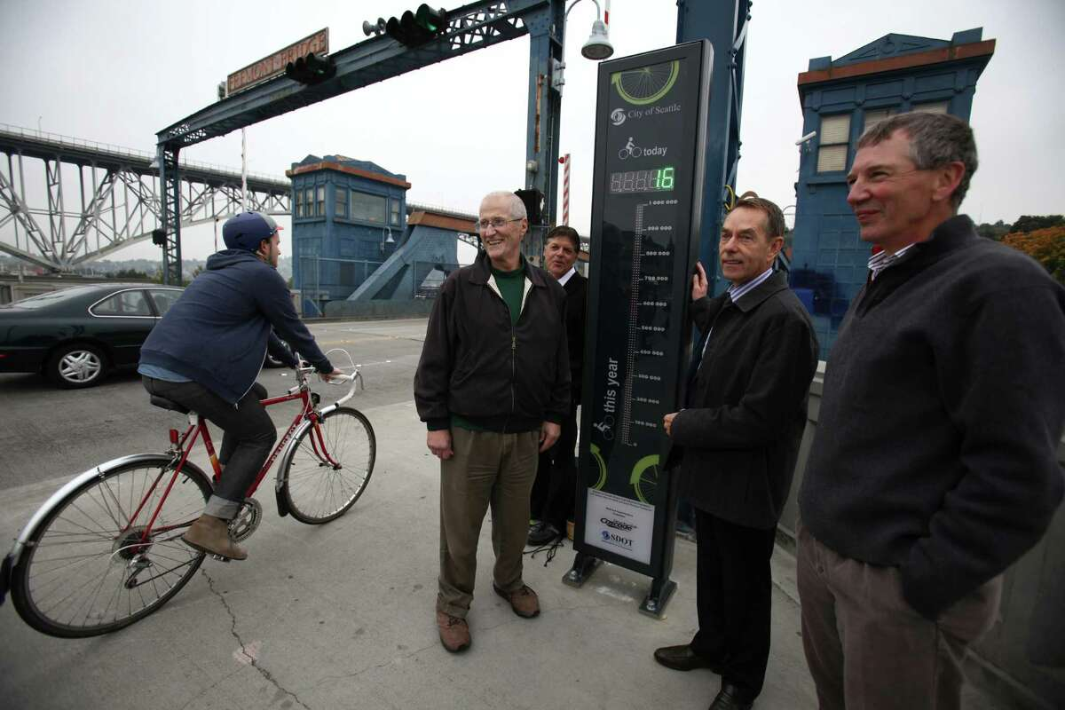 From left, Peter Hahn of SDOT, Mark Torrance, City Councilmember Tom Rasmussen, and Chuck Ayers, executive director at Cascade Bicycle Club watch as bicycles are ridden past after a bicycle counter was unveiled on the Fremont Bridge on Thursday, October 11, 2012 in Seattle's Fremont neighborhood. The counter will provide data on bicycle use on the popular route, similar to data available for automobiles.