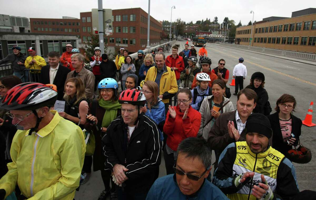 Bicycle riders and spectators applaud as a new bike counter is unveiled on the Fremont Bridge on Thursday, October 11, 2012 in Seattle's Fremont neighborhood. The counter will provide data on bicycle use on the popular route, similar to data available for automobiles.