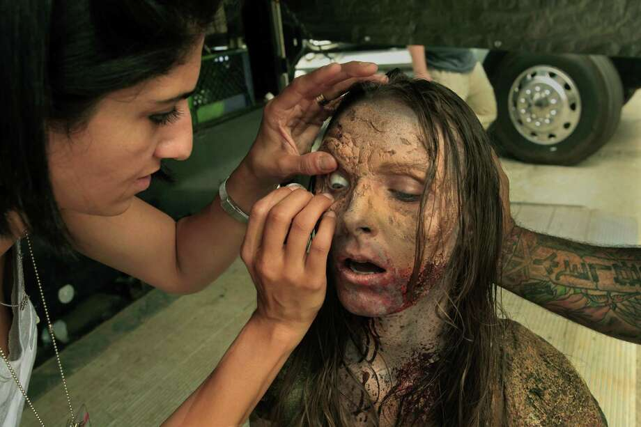 Amanda Adams has a fake eye put on her as he is made up for the role of a zombie. Photo: Carolyn Cole, McClatchy-Tribune News Service / Los Angeles Times