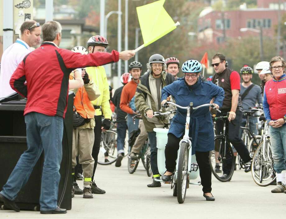 Riders begin to cross a sensor as a new bike counter is unveiled on the Fremont Bridge on Thursday, October 11, 2012 in Seattle's Fremont neighborhood. The counter will provide data on bicycle use on the popular route, similar to data available for automobiles. Photo: JOSHUA TRUJILLO / SEATTLEPI.COM