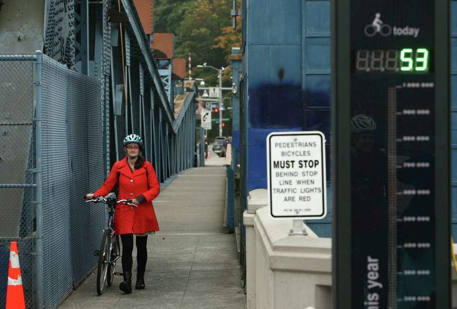 A rider walks her bike after a new bike counter was unveiled on the Fremont Bridge on Thursday, October 11, 2012 in Seattle's Fremont neighborhood. The counter will provide data on bicycle use on the popular route, similar to data available for automobiles. Photo: JOSHUA TRUJILLO / SEATTLEPI.COM