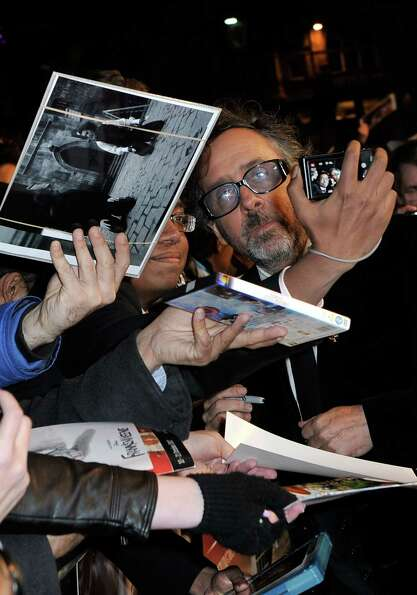 Filmmaker Tim Burton  takes a photo with a fan at the opening night film of the 56th BFI London Film