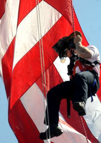 A Beaumont fireman repels from the top of a ladder truck during Dogtoberfest downtown Beaumont, Saturday. Tammy McKinley/The Enterprise Photo: TAMMY MCKINLEY, MBR / Beaumont