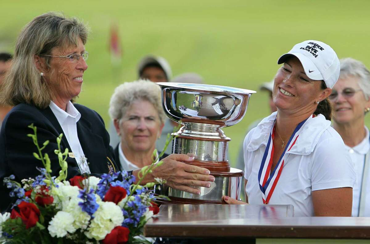 USGA's Barbara Barrow (left) hands the winner's trophy to Meghan Stasi of Oakland Park, Florida after Stasi defeated Liz Waynick of Scottsdale, Arizona, 6&5, at the USGA U.S. Women's Mid-Amateur Championships at Briggs Ranch Golf Club on Thursday, Oct. 11, 2012. Stasi won the title for the fourth time.