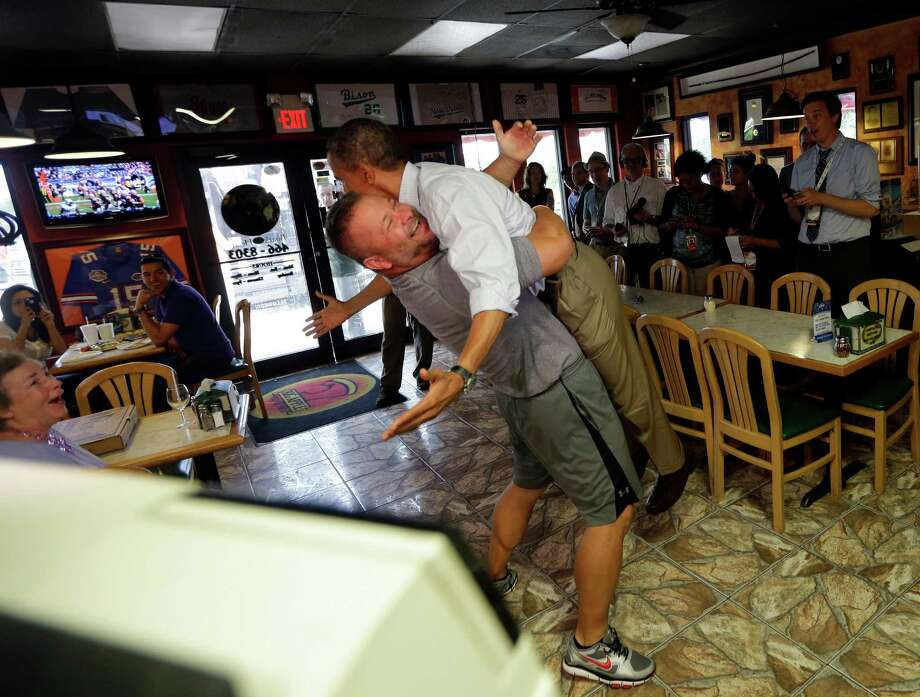 In this Sept. 9, 2012 file photo, President Barack Obama goes airborne in a doozie of a bear hug from Scott Van Duzer, left, owner of Big Apple Pizza and Pasta Italian Restaurant during an unannounced stop in Ft. Pierce, Fla.  Photo: Pablo Martinez Monsivais, Ap / AP