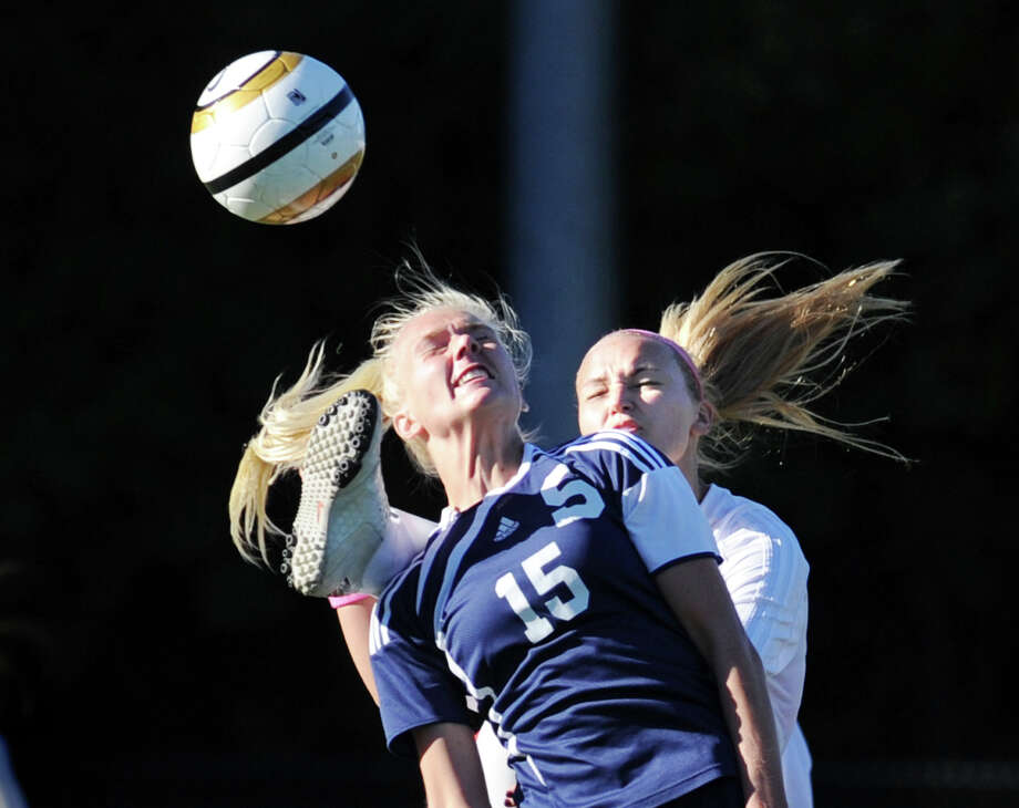 At left, Ryan Kirshner # 15 of Staples goes for the ball while nearing taking the foot of Emily Johnson of Greenwich to her head during the first half of the girls high school soccer match between Greenwich High School and Staples High School at Greenwich, Thursday, Oct. 11, 2012. Photo: Bob Luckey / Greenwich Time