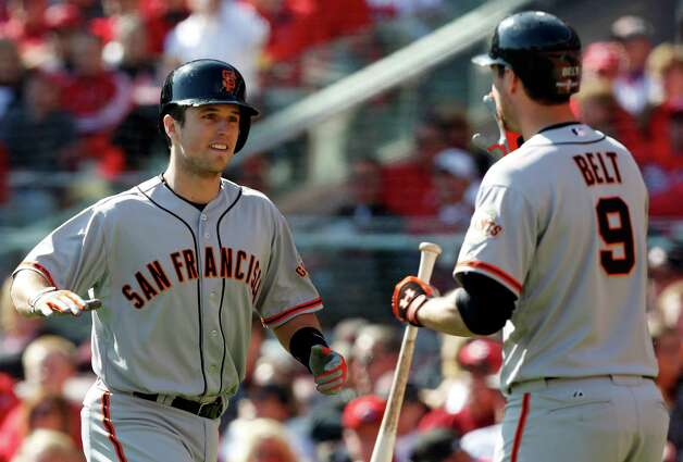 San Francisco Giants' Buster Posey is congratulated by Brandon Belt (9) after Posey hit a grand slam against the Cincinnati Reds in the fifth inning of Game 5 of the National League division baseball series, Thursday, Oct. 11, 2012, in Cincinnati. (AP Photo/David Kohl) Photo: David Kohl, FRE / FR51830 AP