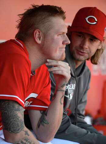 Cincinnati Reds starting pitcher Mat Latos sits in the dugout with Bronson Arroyo, right, after Latos gave up a grand slam to San Francisco Giants' Buster Posey in the fifth inning of Game 5 of the National League division baseball series, Thursday, Oct. 11, 2012, in Cincinnati. (AP Photo/Michael Keating) Photo: Michael Keating, FRE / FR170759 AP