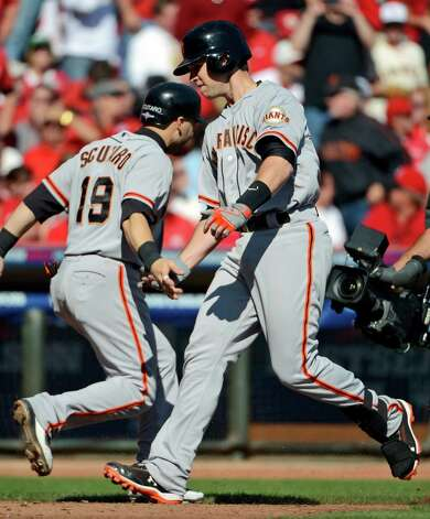 San Francisco Giants' Buster Posey is congratulated by Marco Scutaro (19) after Posey hit a grand slam against the Cincinnati Reds in the fifth inning of Game 5 of the National League division baseball series, Thursday, Oct. 11, 2012, in Cincinnati. (AP Photo/Michael Keating) Photo: Michael Keating, FRE / FR170759 AP