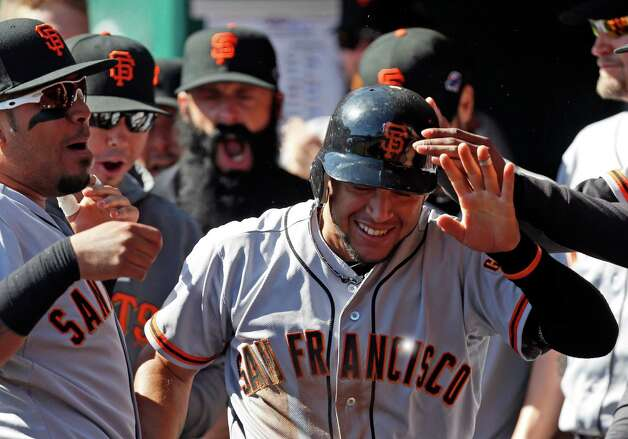 San Francisco Giants' Gregor Blanco, right, is congratulated in the dugout after scoring the first run of the game in the fifth inning of Game 5 of the National League division baseball series against the Cincinnati Reds, Thursday, Oct. 11, 2012, in Cincinnati. Blanco scored from first on an RBI triple by Brandon Crawford. (AP Photo/David Kohl) Photo: David Kohl, FRE / FR51830 AP