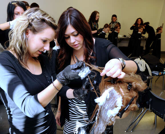 Gabrielle McGrath, left, a student at Paul Mitchell The School, works with Jaimie Verrastro, a learning leader, Thursday, Oct. 11, 2012. Photo: Carol Kaliff