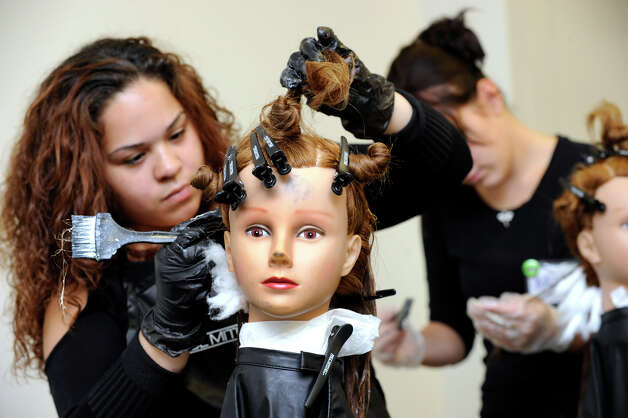 Angelina Vazquez, of Waterbury, uses a mannequin head to work on hair color at Paul Mitchell The School in Danbury, Thursday, Oct. 11, 2012. Photo: Carol Kaliff