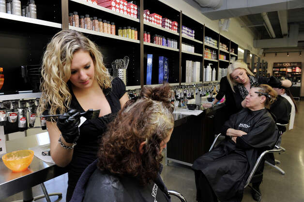 Jessica Sasso of Danbury, left, a student at Paul Mitchell The School colors a client's hair Thursday, Oct. 11, 2012. Photo: Carol Kaliff