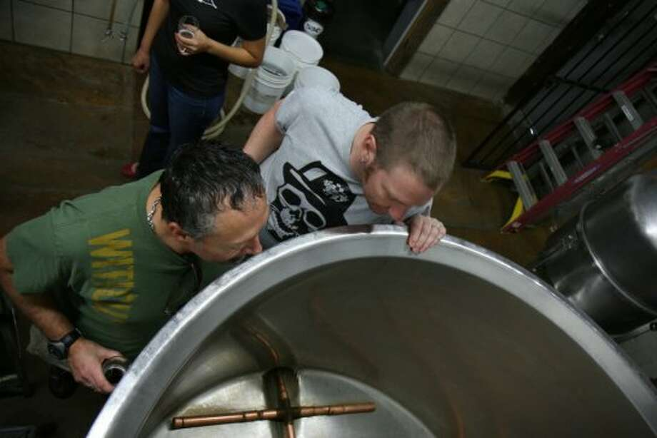 Homebrewers Aaron Shakocius (left) and Jason Murdoch peer into Strange Brewing's mash tun, a converted dairy tank. (Markus Haas / San Antonio Express-News)