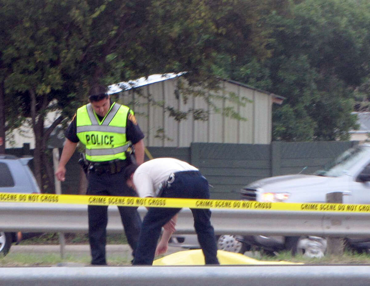Police examine the site where a woman was killed while trying to cross Highway 90 at Military Drive on Thursday, Oct. 11, 2012.