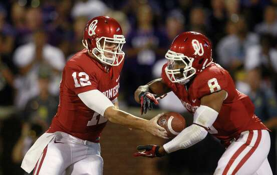 Oklahoma quarterback Landry Jones (12) hands off to running back Dominique Whaley (8) during an NCAA college football game against Kansas State in Norman, Okla., Saturday, Sept. 22, 2012. Kansas State won 24-19. Photo: Sue Ogrocki, Associated Press / AP